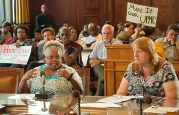 UPMC Employees Teri Collins and Kathy Cabbagestalk testify at a Pittsburgh City Council hearing.